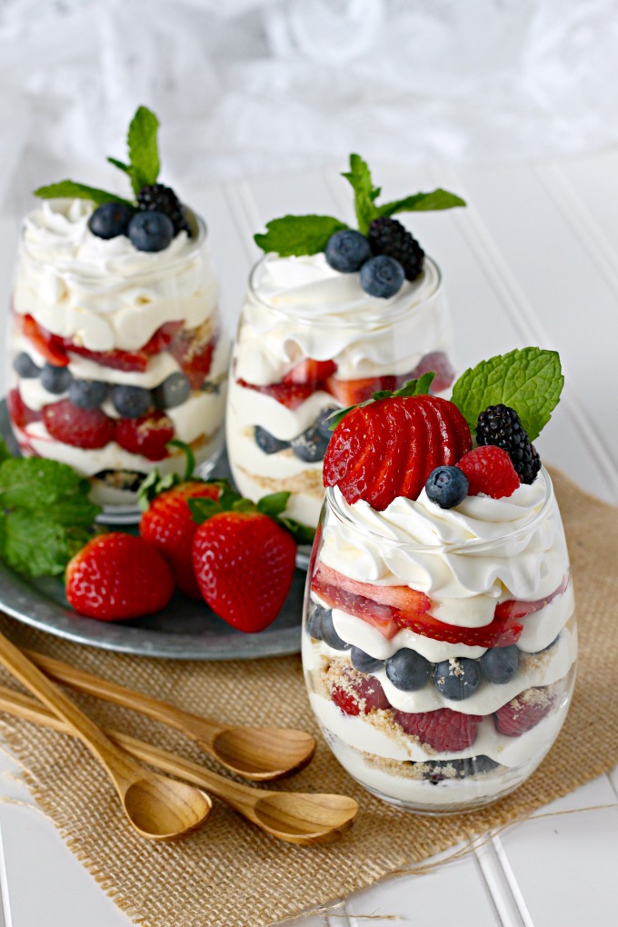Individual berry cheesecake trifles with strawberries, blueberries, raspberries, blackberries, and no-bake cheesecake pudding mousse.
