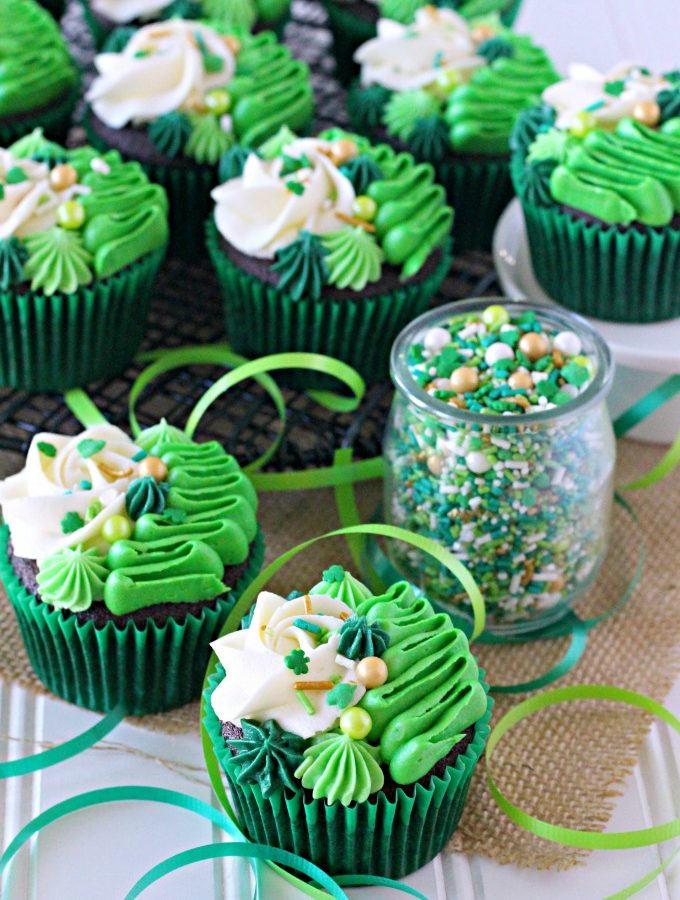 Irish Cream chocolate cupcakes topped with white and green buttercream piping and shamrock sprinkle mix