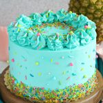 PIneapple cake with pineapple curd, teal frosting and tropical sprinkle mix