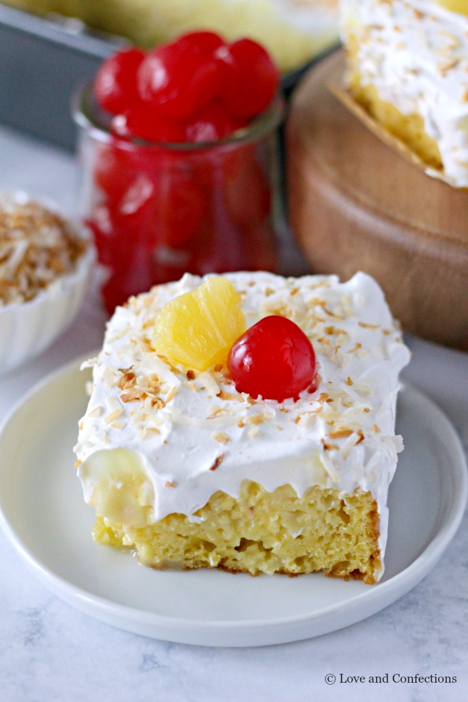 Easy Piña Colada Poke Cake - pineapple cake, coconut cream pudding, whipped topping, pineapple chunks and maraschino cherries