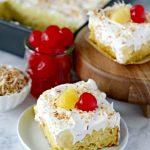 Easy Piña Colada Poke Cake - pineapple cake, coconut cream pudding, whipped topping, pineapple chunks and maraschino cherries